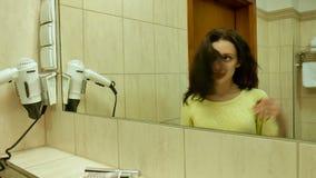 Retrato do close up da cara fêmea com pele limpa no espelho A menina de sorriso nova com cabelo encaracolado escuro está olhando filme