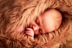 retrato do close up da cara recém-nascida do sono do bebê com mão sob o mordente Fotos de Stock Royalty Free