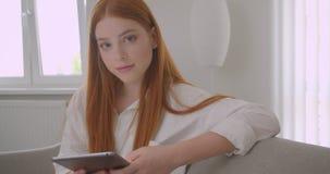Retrato do close up da fêmea bonita nova do ruivo que consulta a tabuleta e que olha a câmera que sorri alegremente sentando-se s video estoque