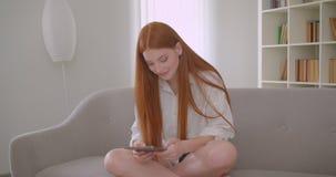 Retrato do close up da fêmea bonita nova do ruivo que consulta a tabuleta que senta-se no sofá em um apartamento acolhedor filme