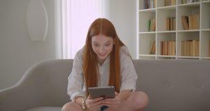 Retrato do close up da fêmea bonita nova do ruivo que manda um vídeo chamar a tabuleta que fala com o excitamento que senta-se no filme