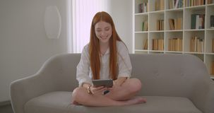 Retrato do close up da fêmea bonita nova do ruivo que manda um vídeo chamar a tabuleta que senta-se no sofá em um acolhedor video estoque