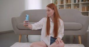Retrato do close up da fêmea bonita nova do ruivo que toma selfies no telefone que senta-se no assoalho em um apartamento acolhed filme