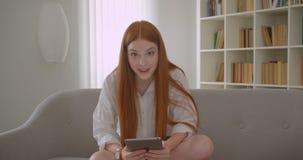 Retrato do close up da fêmea bonita nova do ruivo que usa a tabuleta que ri felizmente olhando a câmera ao sentar-se no video estoque