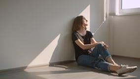 Retrato do close up da fêmea caucasiano alegre nova que senta-se no assoalho pela janela que sorri felizmente dentro no acolhedor