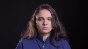 Retrato do close up da fêmea caucasiano atrativa adulta com o cabelo moreno longo que é câmera triste e desapontado com filme
