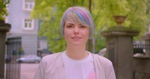 Retrato do close up da fêmea caucasiano bonita nova com o cabelo tingido que olha a câmera fora no parque filme
