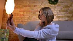 Retrato do close up da fêmea caucasiano bonita nova que toma selfies no telefone que está em casa em um apartamento acolhedor den filme