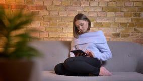 Retrato do close up da fêmea caucasiano bonita nova que usa a tabuleta ao sentar-se no sofá na casa acolhedor dentro filme