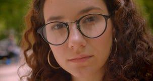 Retrato do close up da fêmea caucasiano encaracolado de cabelos compridos bonita nova nos vidros que olham a câmera fora no jardi filme