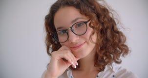 Retrato do close up da fêmea caucasiano encaracolado de cabelos compridos bonita nova nos vidros que sorri felizmente olhando a c