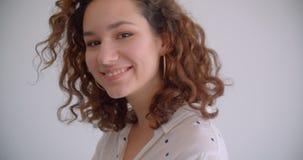 Retrato do close up da fêmea caucasiano encaracolado de cabelos compridos bonita nova que lanç seu cabelo que sorri felizmente ol