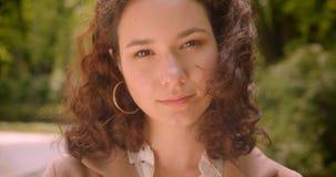 Retrato do close up da fêmea caucasiano encaracolado de cabelos compridos bonita nova que olha alegremente a câmera que está fora filme