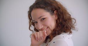 Retrato do close up da fêmea caucasiano encaracolado de cabelos compridos bonita nova que põe seu dedo aos bordos que sorriem fel