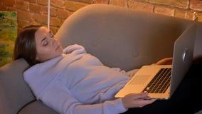 Retrato do close up da fêmea caucasiano nova que usa o portátil que encontra-se no sofá dentro vídeos de arquivo