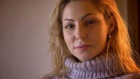Retrato do close up da fêmea loura caucasiano bonita adulta que olha a câmera e que sorri seductively em um apartamento acolhedor