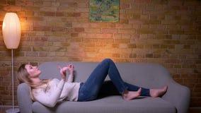 Retrato do close up da fêmea moreno caucasiano atrativa nova que escuta a música e o encontro de relaxamento no sofá filme