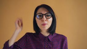 Retrato do close-up da gritaria irritada e de agitar da jovem mulher os braços batendo principais video estoque