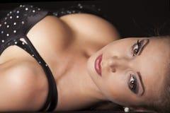 Retrato do close-up da jovem mulher bonita na obscuridade - fundo azul Fotos de Stock Royalty Free