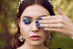 Retrato do close up da jovem mulher com composição azul brilhante e tratamento de mãos azul, decoração azul Composição e tratamen imagem de stock