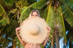Retrato do close up da jovem mulher que guarda o chap?u de palha grande, tempo ensolarado tropical de aprecia??o f?mea bonito foto de stock royalty free