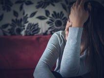 Retrato do close up da jovem mulher triste que senta-se pelo sofá em casa fotografia de stock royalty free