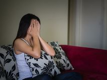 Retrato do close up da jovem mulher triste que senta-se pelo sofá em casa imagens de stock