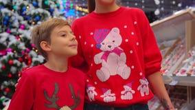 Retrato do close-up da mãe e do filho alegres em ligações em ponte engraçadas do Natal que andam ao longo do shopping e filme