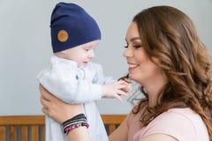 Retrato do close-up da mãe nova feliz que abraça e que beija sua criança adorável doce Disparou dentro, imagem do conceito Fotografia de Stock