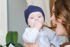 Retrato do close-up da mãe nova feliz que abraça e que beija sua criança adorável doce Disparou dentro, imagem do conceito Imagem de Stock