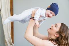 Retrato do close-up da mãe nova feliz que abraça e que beija sua criança adorável doce Disparou dentro, imagem do conceito Imagens de Stock