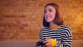 Retrato do close up da menina alegre nova que joga jogos de vídeo usando o console do jogo que mante distraído o assento no sofá  filme