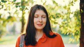 Retrato do close-up da menina bonita com o cabelo marrom que olha a câmera e que sorri com o parque do verão no fundo vídeos de arquivo