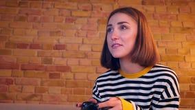 Retrato do close up da menina bonita nova que joga jogos de vídeo usando o console do jogo e sendo assento feliz no sofá dentro filme