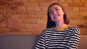 Retrato do close up da menina bonita nova que olha uma comédia na tevê que ri felizmente o assento no sofá que está sendo relaxad vídeos de arquivo