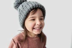 Retrato do close up da menina bonito feliz na camiseta cinzenta morna do chapéu do inverno, do sorriso e vestir isolada em um est fotografia de stock