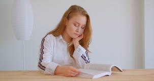 Retrato do close up da menina caucasiano bonita nova que estuda e que lê um livro dentro no apartamento vídeos de arquivo
