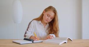 Retrato do close up da menina caucasiano bonita nova que estuda e que toma notas dentro no apartamento filme