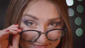 Retrato do close up da menina caucasiano bonita nova que fixa seus vidros e que aumenta a sobrancelha que olha a câmera que sorri filme