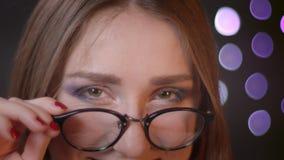 Retrato do close up da menina caucasiano bonita nova que fixa seus vidros e que aumenta a sobrancelha que olha flertar da câmera filme