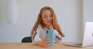Retrato do close up da menina caucasiano bonita nova que manda um vídeo chamar o telefone que senta-se na frente do portátil dent vídeos de arquivo