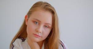 Retrato do close up da menina caucasiano bonita nova que olha a câmera dentro com o fundo isolado no branco vídeos de arquivo