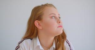 Retrato do close up da menina caucasiano bonita nova que olha a câmera que sorri alegremente dentro no apartamento video estoque