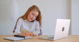 Retrato do close up da menina caucasiano bonita nova que tem um telefonema no telefone que datilografa no portátil dentro no vídeos de arquivo