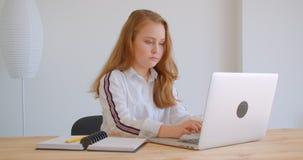 Retrato do close up da menina caucasiano bonita nova que usa o latop dentro no apartamento filme