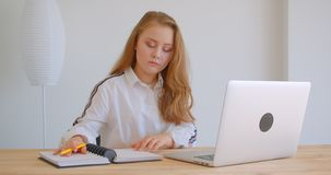 Retrato do close up da menina caucasiano bonita nova que usa o latop e estudando em linha dentro no apartamento filme