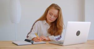 Retrato do close up da menina caucasiano bonita nova que usa o latop e estudando tomando notas dentro no apartamento video estoque