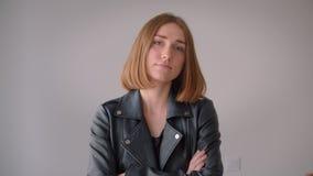 Retrato do close up da menina caucasiano bonito nova em um casaco de cabedal que tem seus braços cruzados olhando a câmera dentro