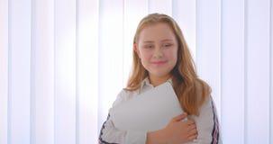 Retrato do close up da menina caucasiano bonito nova que guarda um portátil que está dentro no apartamento vídeos de arquivo