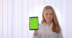 Retrato do close up da menina caucasiano bonito nova que usa uma tabuleta e mostrando a tela verde à câmera que está dentro no video estoque